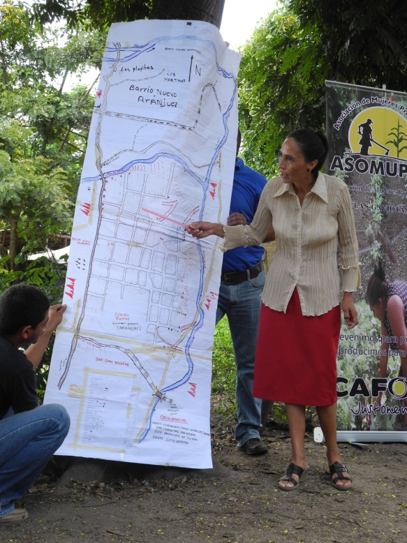 Women's group leader showcasing their community hazard map in Nicaragua.