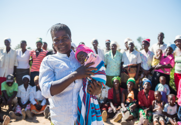Marian stands proudly with other members of Chinyama community vegetable garden, holding her two-month-old baby girl Talent.