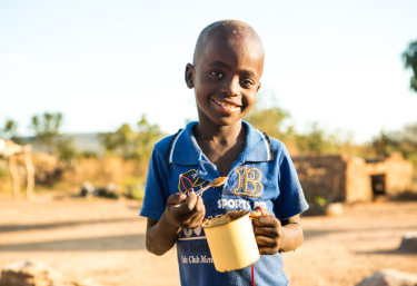 Svondo, 7 years old, enjoying peanut butter. He is healthy. Thanks to CAFOD's partner who supported his mum, Marian with vegetables seeds and training..