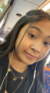 Young girl sitting on a bus with brown hair and earphones in wearing butterfly necklace and grey t shirt